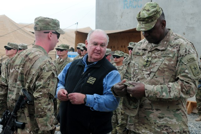 Staff Sgt. Brian Starrs of A Company, 1st Infantry Regiment, 2nd Stryker Brigade Combat Team, 2nd Infantry Division, is promoted by Undersecretary Army Joseph W. Westphal and Vice Chief of Staff of the Army Gen. Lloyd J. Austin III during a Thanksgiving visit to Combat Outpost Sanjeray, Afghanistan, Nov. 22, 2012.  The Army officials visited the base and several others to show Soldiers their appreciation.