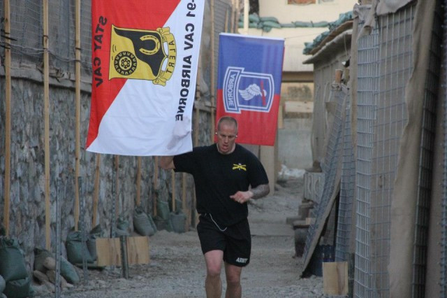 Capt. Jonathan Pankake, participating in the Running of the Herd event, runs through the hall of heroes set up on command post Baraki Barack in Afghanistan Nov. 8. A total of 140 Comanche Troop Soldiers, from the 1st Squadron 91st Cavalry Regiment, ran more than 1200 miles to help raise over $70,000 for the Wounded Warrior Project.