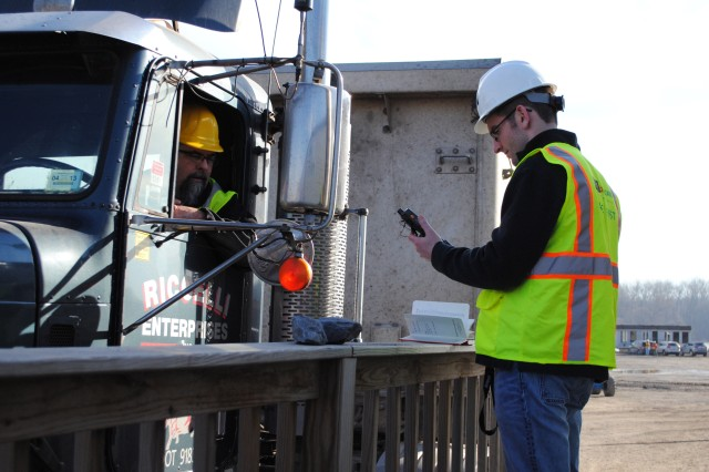 Matt Hross, a systems technician with Arcadis, logs a truck into HaulPass, an automated debris management system that utilizes GPS technology, while Dan Potter, a truck driver from Liverpool, N.Y., look on Nov. 23, 2012, at the Port of Coeymans, near Albany, N.Y. Rather than using manual ticket data entry, the U.S. Army Corps of Engineers is using HaulPass to ensure accountability for trucks and load quantities.