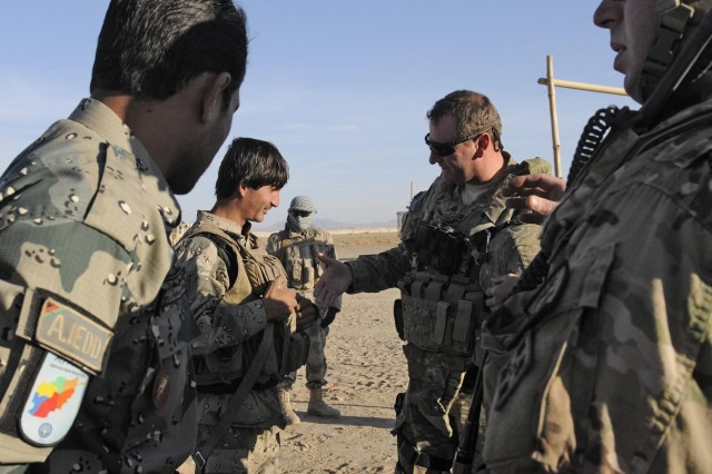 Lt. Col. Scott Sill, an Afghan Hand and senior mentor with Security Forces Assistance Team 11, greets a member of the Afghan Border Police during Operation Southern Strike IV, Kandahar Province, Afghanistan, Nov. 15, 2012. The operation focused on removing insurgent influence on the local population and connecting isolated villages to their government and police.