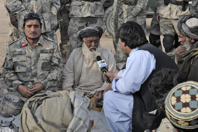 Afghan Brig. Gen. Tasfir Khan, commander of the 3rd Zone Afghan Border Police, listens as an Afghan news reporter interviews a village elder during Operation Southern Strike IV, Kandahar Province, Afghanistan, Nov. 15, 2012. The operation focused on removing insurgent influence on the local population and connecting isolated villages to their government and police.