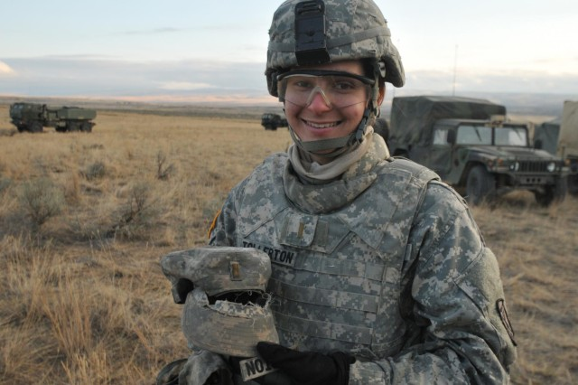 During a training exercise at Yakima Training Center, 2nd Lt. Michael Tollerton of Sarasota, Fla., a platoon leader with Company A, 1st Battalion, 94th Field Artillery Regiment, 17th Fires Brigade, shows the remains of her hat after soldiers taped it to a High Mobility Artillery Rocket System at Yakima Training Center, Nov. 9.