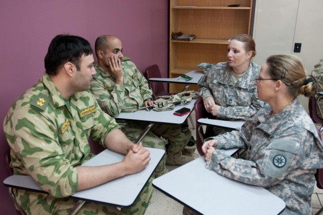 Kuwait National Guard 1st Lt. Hashem Al-Refae and 1st Lt. Hamad Al-Shetail sit with Lt. Col. Ines Berger and  Master Sgt. Michelle Shimps, members of the 316th Sustainment Command (Expeditionary), to discuss tactical combat casualty care. The Kuwait National Guard officers attended the combat lifesaver course to participate and share experiences on how the Kuwait National Guard and the U.S. Army conducts medical training to non-medical personnel.