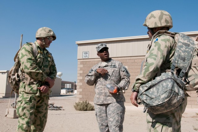 U.S. Army Staff Sgt. Roderick Evans, a medic with Army Support Group - Kuwait, briefs Kuwait National Guard 1st Lt. Hashem Al-Refae and 1st Lt. Hamad Al-Shetail before the combat lifesaver class practical exercise. The practical exercise is designed to simulate a combat situation where Soldiers gain fire superiority, stop their patients' bleeding and then get them to cover where they can call for help. The Kuwait National Guard soldiers attended to observe how the U.S. Army conducts medical training to non-medical personnel.