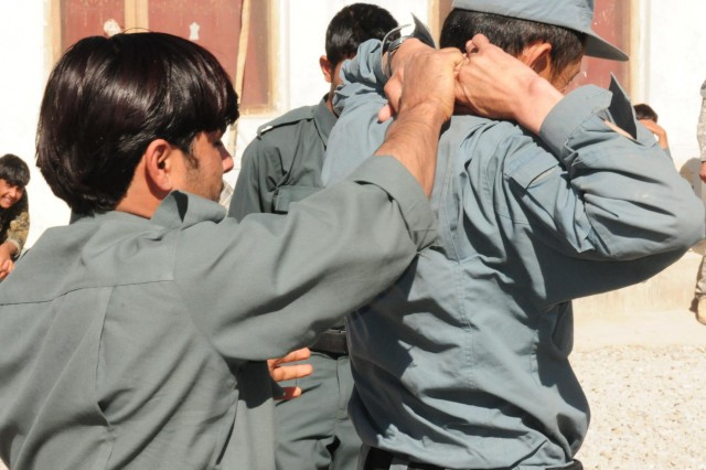 An Afghan Uniform Police officer uses techniques learned from Security Forces Advisory Team 28 to thoroughly search the driver at the Provincial Sub Station, Tarin Kot, Afghanistan, Nov. 12, 2012.