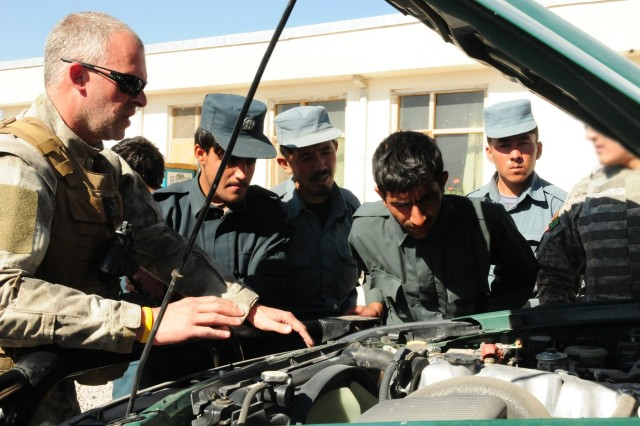 Jim O'Leary, Dynacorps International police officer, explains how thorough search techniques are crucial to the overall search as the Afghan Uniform Police look at the vehicles engine at the Provincial Sub Station, Tarin Kot, Afghanistan, Nov. 12, 2012.