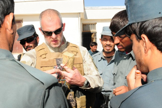 Jim O'Leary, Dynacorps International police officer, holds a training explosive device found on a vehicle as the Afghan Uniform Police get a closer look at the Provincial Sub Station, Tarin Kot, Afghanistan, Nov. 12, 2012.