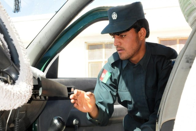 Abdul Wali, an Afghan Uniform Police officer, searches a vehicle for weapons and explosive devices at the Provincial Sub Station, Tarin Kot, Afghanistan, Nov. 12, 2012.