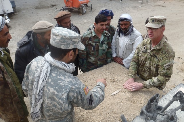 Lt. Col. Greg Wooten, 605th Survey and Design Engineer Detachment commander, discusses operation plans with Afghan partners during Operation Mountain Blade in Parwan province, Afghanistan, recently. The operation, conducted by engineering elements of Joint Task Force Empire, improved the road surface of the pass in preparation for winter.