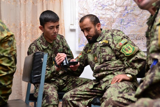 An Afghan National Army Public Affairs soldier from 205th Corps instructs a 4th Brigade public affairs soldier on video techniques during Operation Kalak Hode VI in the 205th Corps joint Tactical Operations Center in Tarin Kot, Uruzgan, Nov. 11, 2012.