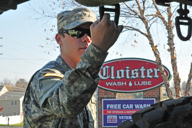 Spc. Tyler Mcclucas, a motor transportation specialist with the 733rd Transportation Company out of Reading, Pa, conducts preventive maintenance checks on a Palletized Load System while on display at the free car wash for veterans held by Cloister wash and lube, Nov. 11, 2012. This is the 8th consecutive year that Cloister wash and lube honors veterans with a free car wash.