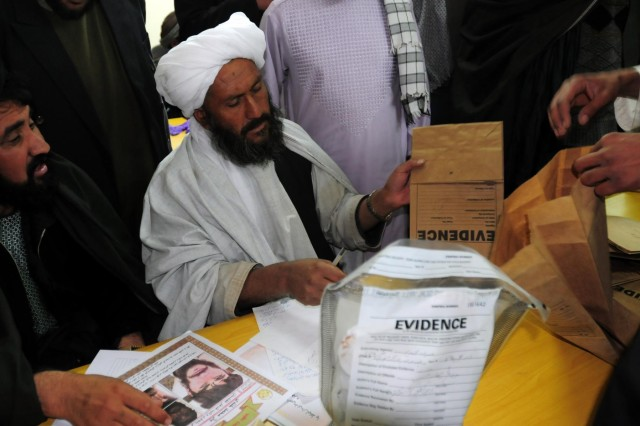 Members of the jury sort through evidence to determine a verdict in the homicide case at Multi National Base Tarin Kot, Afghanistan, Nov. 21, 2012.