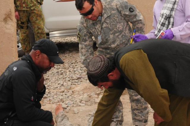 Mirwais Ghani, Evidence Based Police Operations student (bottom right), checks the victim's pulse before proceeding to collect evidence on the homicide scene at Multi National Base Tarin Kot, Afghanistan, Nov. 21, 2012.