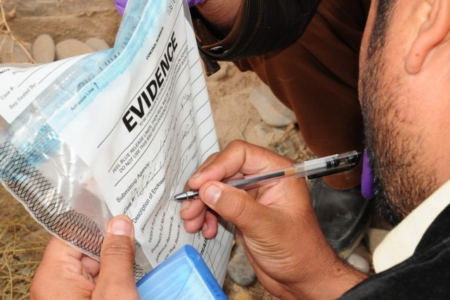 Hejratullah Zaheer, investigative prosecutor, properly labels the evidence collected on the homicide case at Multi National Base Tarin Kot, Afghanistan, Nov. 21, 2012.