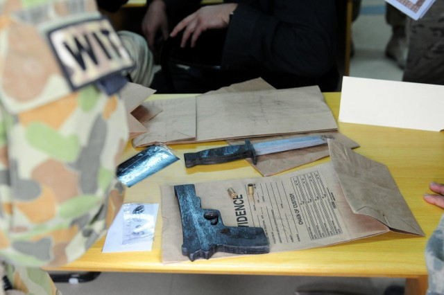 The Weapons Intelligence Team analyzes the evidence, searching for any forensic links to the suspect in the homicide case at Multi National Base Tarin Kot, Afghanistan, Nov. 21, 2012.