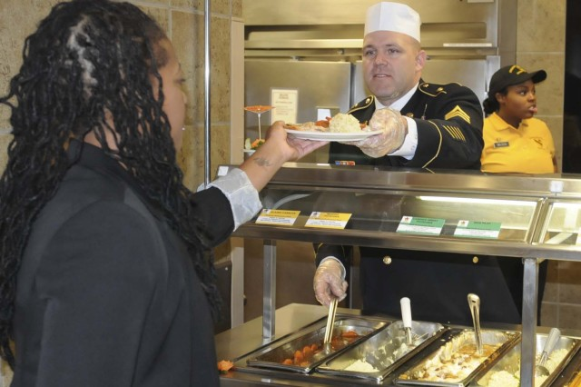 "FORT HOOD, Texas--Sgt. 1st Class Jayson Mix, a Soldier with 3rd ""GreyWolf"" Brigade Combat Team, 1st Cavalry Division, helps serve a Thanksgiving meal at the Operation Iraqi Freedom Dining Facility on Nov. 22, at here."