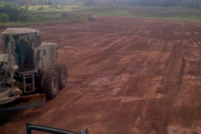 Soldiers with the 523rd Engineer Company, 84th Engineer Battalion, 130th Engineer Brigade, 8th Theater Sustainment Command, operate a grader and put the final grade to the Kane's Drop Zone while a far away roller compacts and smooths the surface of a road for future Air Force missions during the months of September and October.
