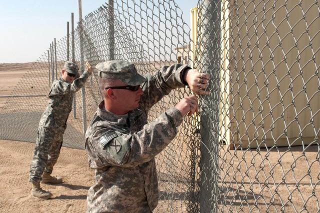 Aided by another soldier, Spc. Gabriel Wilson (center) erects a fence to enclose the Convenience Center at Camp Buehring, Kuwait. The center is designed so troops and other camp personnel can leave second-hand items for others who need them. Wilson conceived the idea for the facility, which is also expected to promote recycling and reduce illegal dumping in the camp. Wilson, of Longs, S.C., is a member of the 4th Battalion, 118th Infantry Regiment, South Carolina Army National Guard, which assumed camp operations and security-force missions in Northern Kuwait in April. (U.S. Army photo by Sgt. 1st Class Raymond Drumsta, Camp Buehring Public Affairs)