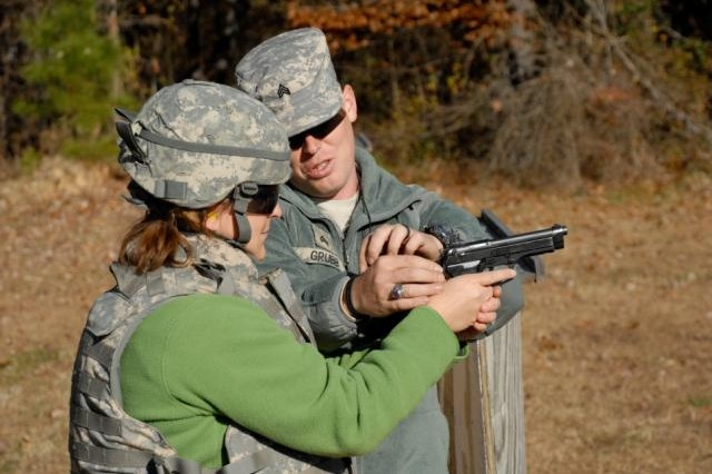 "29th IN DIV Soldier provides hands on 9MM Pistol familiarization training to Ms. Lisa Skinner during Fort AP Hill's inaugural ""Boots on the Ground"" event  on 17 November."