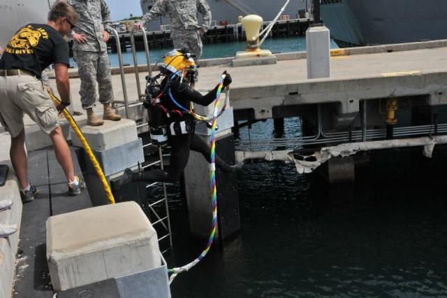 Members of the 7th Dive Detachment, 65th Engineer Battalion, 130th Engineer Brigade, 8th Theater Sustainment Command, A diver enters the water and others stand by to assist to conduct the Shallow Brown exercise which focuses on critical Second Class/Salvage Diver Level Tasks at K-10 Pier, Sep. 28.
