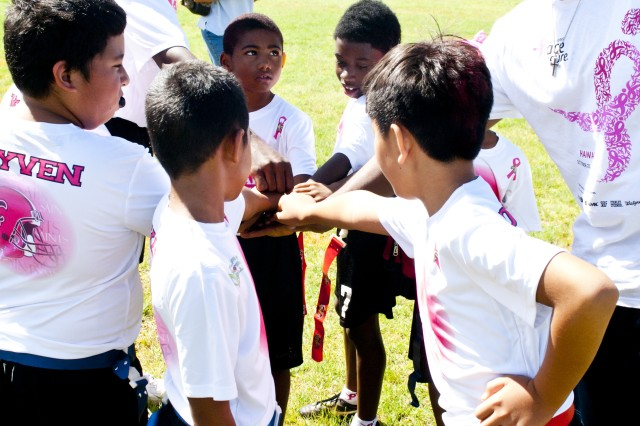 "Sgt. Mark Kerns (top left), 8th TSC, and also coach of the Central Oahu Saints "" a team in the Play Sports Hawaii youth flag football league "" leads some team unity during a recent exhibition game."
