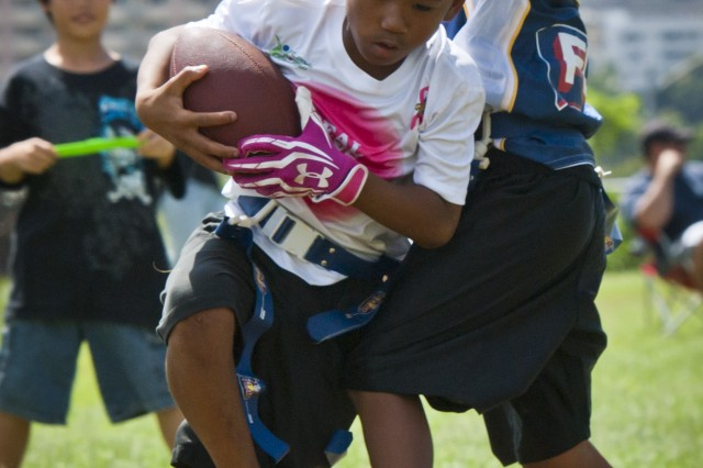 Jydon Hall, quarterback and son of Navy Petty Officer 2nd James Hall, Naval Submarine Support Command, jukes past a defender during a Play Sports Hawaii exhibition game at Ala Puumalu Communty Park, Oct. 21.