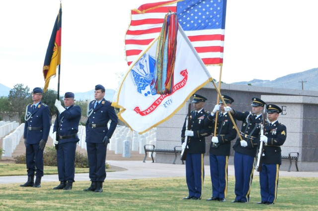Members of the color guard of Headquarters and Headquarters Battery, 402nd Field Artillery Brigade, display the American and Army flags during the German Air Force's observance of Volkstrauertag, or National Day of Mourning, at Fort Bliss National Cemetery Nov. 18. Color guard members pictured are, left to right, Master Sgt. Jerry Silva, Sgt. Richard Hernandez, Sgt. 1st Class Joseph Cline and Sgt. Jonathan Hernandez. (Photo by Staff Sgt. Patricia Deal, 402nd Field Artillery Brigade, Division West, Public Affairs)