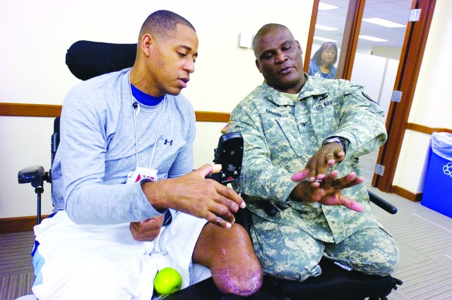 Col. Gregory D. Gadson, Fort Belvoir garrison commander (right) compares his injuries with Sgt. 1st Class Cedric King during a visit with the Warrior Transition Brigade at Walter Reed in Bethesda, Md., on Nov. 21. Gadson spoke to the WTB about his experiences in the Army before and after his injury that cost him his legs in an IED attack in Iraq in 2007.
