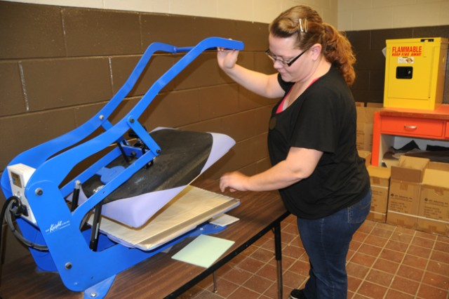 Heather Norris, operations assistant at the arts and craft center, prepares a coaster to be processed in the sublimation machine at the Fort Rucker Arts and Craft Center Nov. 21.