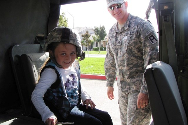 Sara W., a second grade student at George Kelly Elementary School in Tracey, Calif., sits in a Humvee brought to the school by Sgt. 1st Class Earnest Cornwell of 1-363rd Training Support Battalion, 189th Infantry Brigade, Division West, Nov. 8. Eight Soldiers from the 1-363rd visited the school in the bay area to speak to 150 second graders about Veterans Day and their military service. (Photo by Sgt. First Class Victor L. Gardner, 189th Infantry Brigade, Division West, Public Affairs)