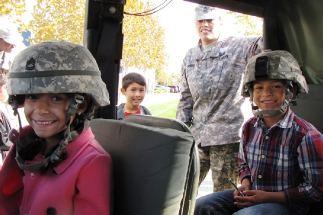 Aliana R. and Gilbert D., second grade students at George Kelly Elementary School in Tracey, Calif., sit in a Humvee brought to the school by Master Sgt. Erika Gordon of 1-363rd Training Support Battalion, 189th Infantry Brigade, Division West, Nov. 8. Eight Soldiers from the 1-363rd visited the school in the bay area to speak to 150 second graders about Veterans Day and their military service. (Photo by Sgt. First Class Victor L. Gardner, 189th Infantry Brigade, Division West, Public Affairs)