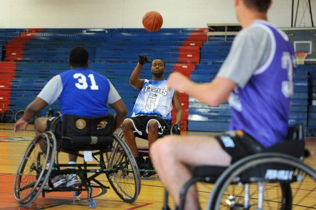 Sgt. Charles Hightower, No. 5, passes the ball to a Co. A teammate during a wheelchair basketball tournament game in the Abrams Physical Fitness Center at Fort Hood, Texas, Nov. 21. (U.S. Army photo by Daniel Cernero, III Corps and Fort Hood Public Affairs)