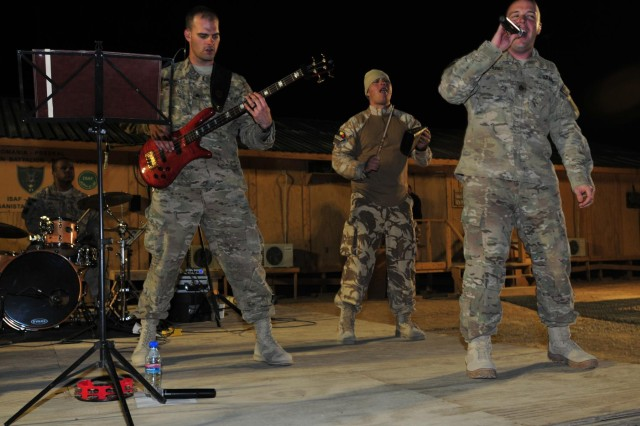 Third Infantry Division rock band members Sgt. Michael Winkler, bass guitarist, and Sgt. Joseph Grabill, vocalist, are joined on stage by Pvt. Marius Tudor, a Romanian soldier playing the cowbell during a Third ID band performance at Forward Operating Base Mescal, Afghanistan, Nov. 14, 2012.  The band's performance was the first live entertainment that the Romanian soldiers of the 21st Mountain Battalion stationed at FOB Mescal have had since arriving in June. (U.S. Army photo by Sgt. Lori Bilyou)