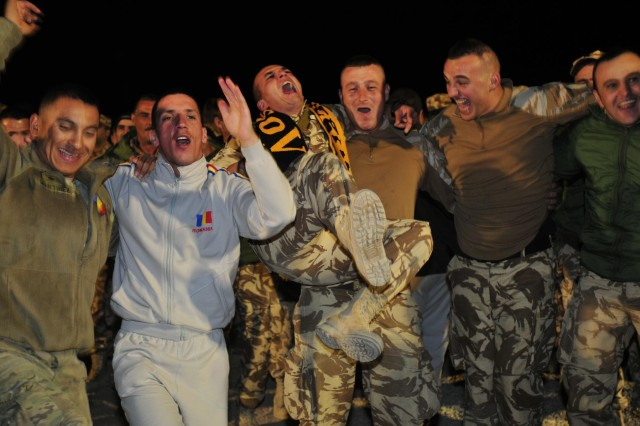 Third Infantry Division band member, saxophone and clarinet player Spc. Tony Martinez and some Romanian soldiers cavort during a performance of the Third ID's rock band, Trigger Happy, at Forward Operating Base Mescal, Afghanistan, Nov. 14, 2012.  The band's performance was the first live entertainment the Romanian soldiers of the 21st Mountain Battalion stationed at FOB Mescal have had since arriving in June. (U.S. Army photo by Sgt. Lori Bilyou)