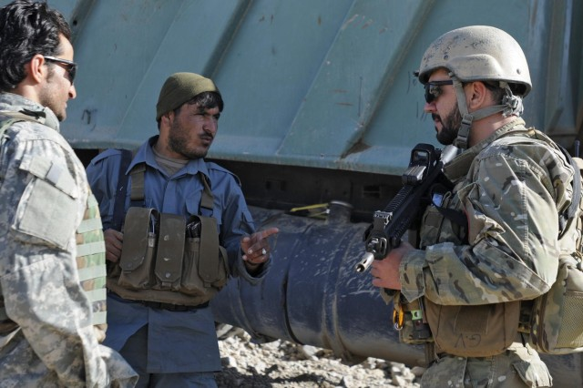An Afghan Uniformed Police member speaks with an Albanian Special Forces member during an assessment of a police sub-station construction project with coalition forces and AUP in Kandahar province, Nov. 7, 2012.