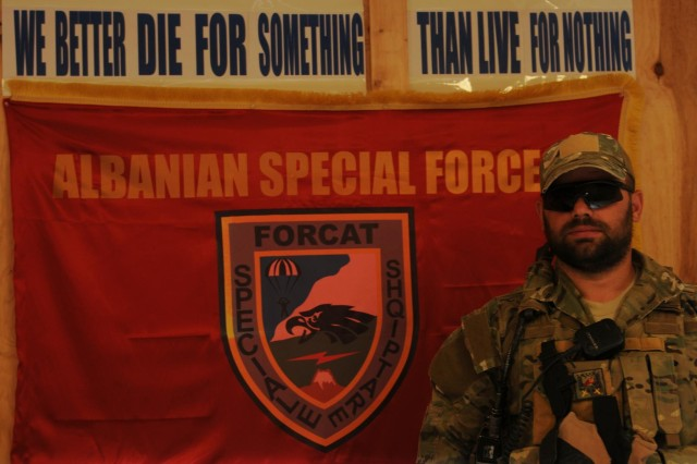 An Albanian Special Forces member with Contingent Eagle Five of the Albanian Special Operations Forces stands near the ALB SOF's motto displayed in Kandahar province, Afghanistan, Nov. 21, 2012.