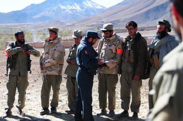 Afghan National Police Col. Noorzai, Khas Uruzgan district chief of police, provides salary to Afghan Local Police members during a key leader visit to Khas Uruzgan district to display their support for the Afghan Peace and Reintegration Program, Nov. 24, 2012.