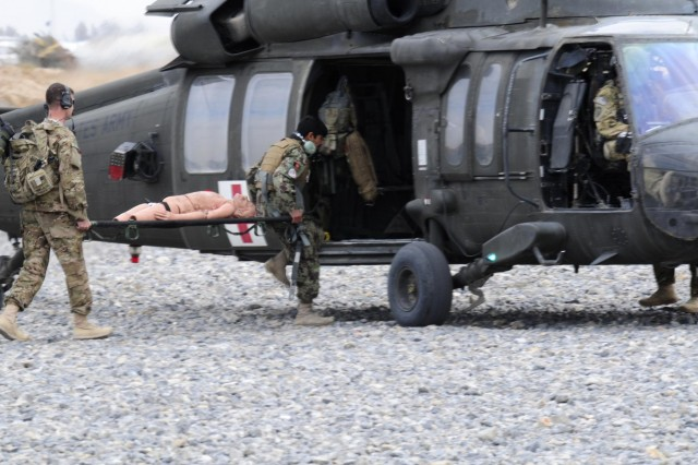 Afghan flight medic Jan Alem, Kandahar Air Wing, loads a simulated patient in the back of a UH-60 medevac Black Hawk assigned to Company C, 3rd Battalion, 25th Aviation Regiment, Task Force Hammerhead, 25th Combat Aviation Brigade, during flight medic training on Kandahar Airfield, Afghanistan, Nov. 28.