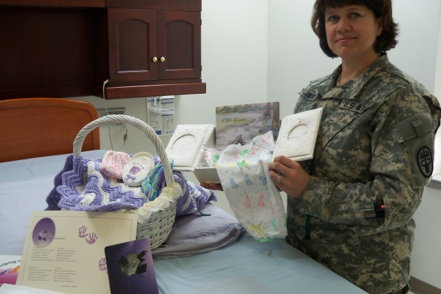 Maj. Dorene Owen, CRDAMC maternal child health clinical nurse specialist, displays bereavement items that are given to parents. (Photo by CRDAMC)