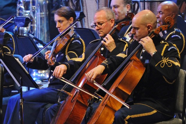 """Members of """"Pershing's Own"""" perform at the annual American Holiday Festival held at DAR Constitution Hall in Washington, D.C., Dec. 2. From left to right: Staff Sgt. Beth Dunkel, violin; Staff Sgt. Samuel Swift, cello and Staff Sgt. Benjamin Wensel, viola."""