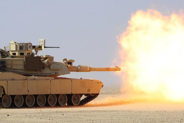 """An M1A2 Main Battle Tank fires at a target during Saweyan Shield, a defensive live-fire exercise, at the Udairi Range Complex near Camp Buehring, Kuwait, Nov. 28. Saweyan is the Arabic word for """"together""""."""