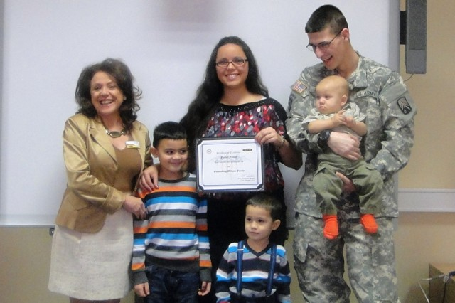 Jolly Miller, ACS director, presents a certificate of appreciation to Elizabeth and Spc. Brenton Feather, along with their three sons, Hayden, Brayden and baby Roman. The family also received a gift basket from the Rose Barracks Commissary.