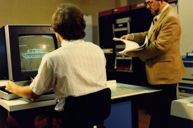 Michael John Muuss (left) using BRL-CAD to visualize the XM1 tank (M1 Abrams prototype) on a Vector General display circa 1980, while Earl Weaver (right) inspects a printout of the XM1 design.