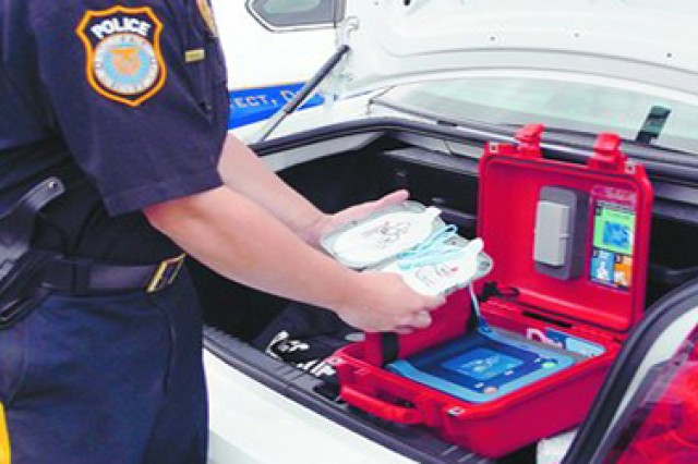 A Ft. Meade police officer inspects an automated external defibrillator stored in the trunk of a patrol vehicle.