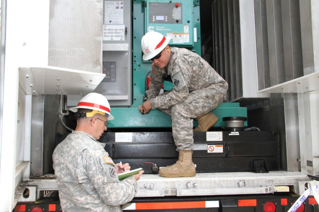 "ROCKAWAY, QUEENS, N.Y. "" Staff Sgt. Henry Howell and Sgt. Nathaniel Boecker of Headquarters and Headquarters Company, 249TH Eng. Battalion (Prime Power), inspect generators at the Ocean Bay Public Housing complex. The 249th has installed 22 generators powering 24 family building structures in the Rockaways."