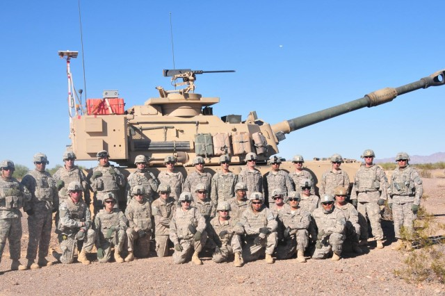 Soldiers of the 4th Battalion, 27th Field Artillery Regiment, 2nd Brigade Combat Team, 1st Armored Division, stand together in front of an M109 Paladin Integrated Management Howitzer while at Yuma Proving Ground, Ariz. The Soldiers of 4-27 FA conducted a series of rigorous tests on the PIM in order to provide accurate, constructive feedback about the self-propelled howitzer.