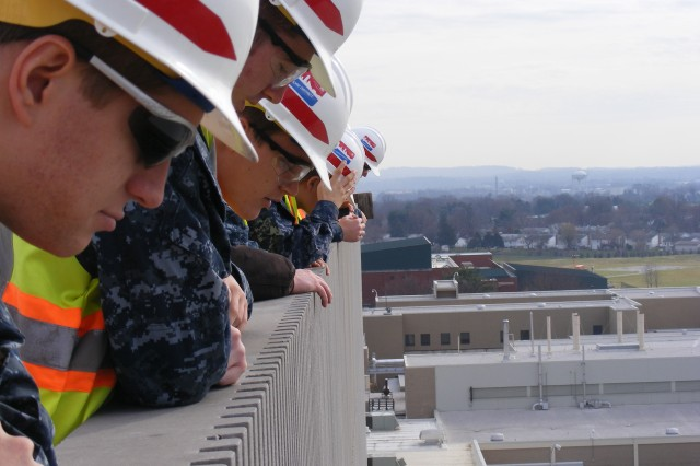 Midshipmen peer over the rooftop edge of the USAMRIID building to get a wider perspective of the National Interagency Biodefense Campus on Fort Detrick, Md.