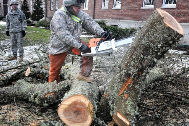 Spc. Sergio Rojas, of 864th Eng. Bn., uses a chainsaw to clear storm debris near Building 2027, Jan. 23. Joint Base Lewis-McChord, Wash., received a heavy snowfall and freezing conditions during the week of Jan. 17-22. Most of the post's personnel stayed home for the week and keep updated on information through the severe weather curtailment program. (Courtesy photo by Scott Hansen, Northwest Guardian)