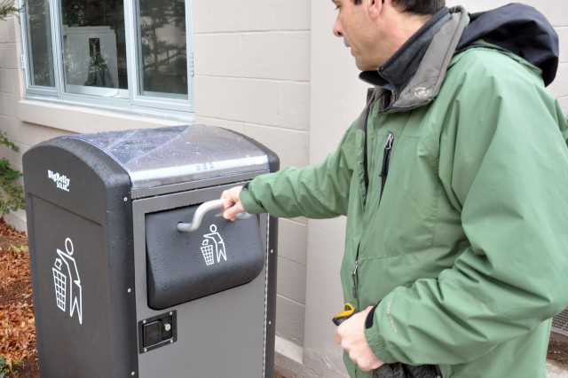 """Rich Valcourt checks on a """"BigBelly"""" solar-powered waste disposal unit at Natick Soldier Systems Center, Mass. NSSC has 12 of the units positioned across the installation."""