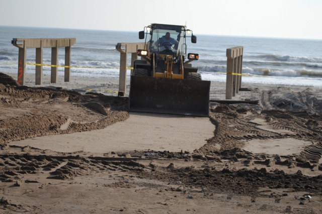 An operator uses a front-end loader to disperse sand around a section of Rockaway Beach heavily impacted by Hurricane Sandy Dec. 4. When Sandy made landfall here last month, it brought a powerful 15-foot storm surge that flooded hundreds of homes, buckled the boardwalk and pushed large parts of the beach into the streets.